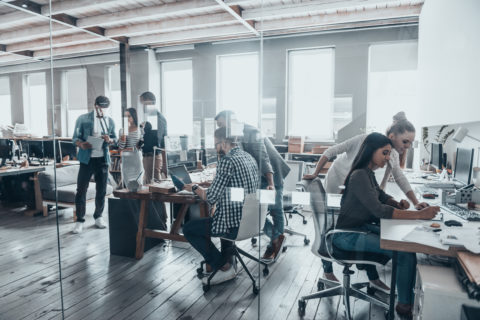 A group of millennial employees are busy collaborating at various workstations in a modern office.