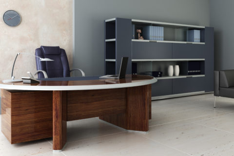 A modern office features a rounded desk with contemporary gray bookshelves with a filing system and part of a black couch.