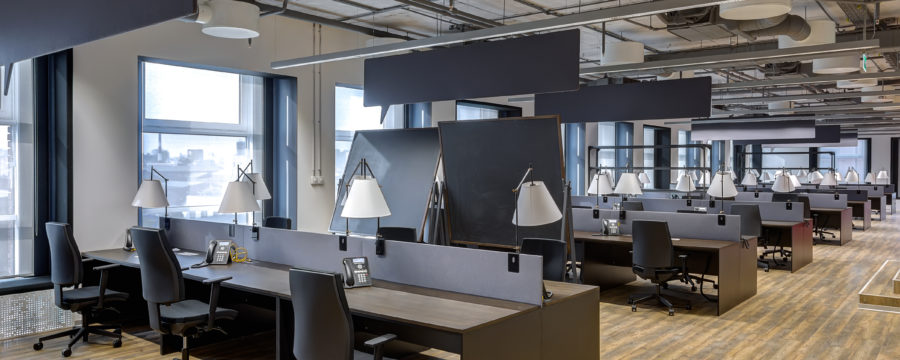 A sleek modern office with wood flooring features shorter cubicles with lamps attached and rolling office chairs.