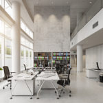 An open, modern workspace features several white tables and desks with black rolling chairs.