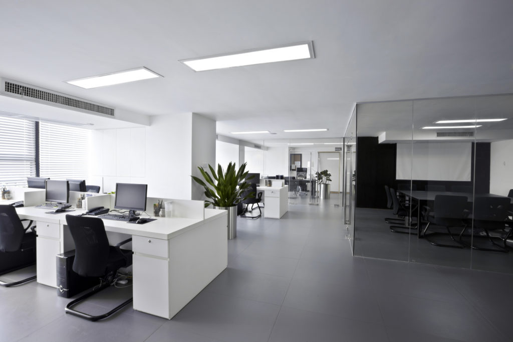 Modern white cubicle clusters with desk pedestals are grouped together in a light and open workspace.