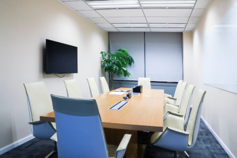 Modern office conference room with a large wooden table, white chairs and a blue carpet.