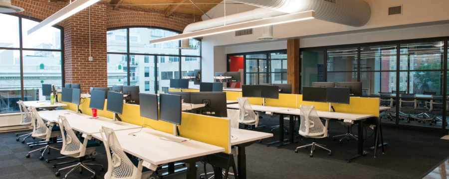 A modern office space reveals individual workstations with plenty of natural lighting and modern light fixtures.