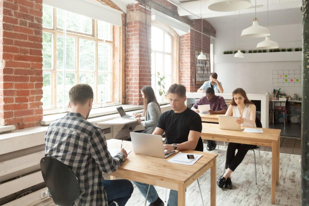 Employees work on laptops at shared desks in a small, open-concept office space with exposed brick and large windows.