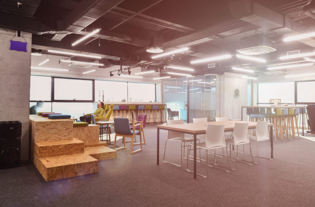 A modern office depicts an open work concept with open desk seating and natural light.