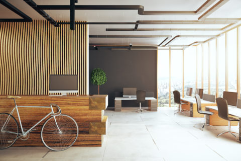 A modern office features an open concept with several desks facing the window and a bike leaning on the reception desk.