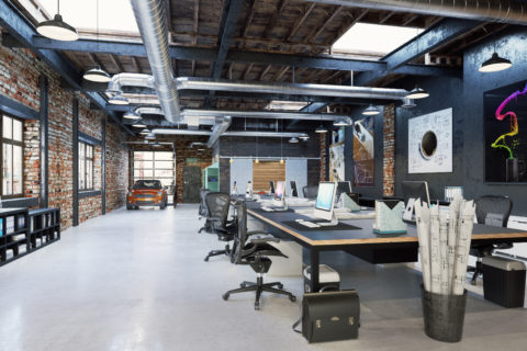 A modern office loft with brick and exposed industrial design shows a common meeting table area with matching chairs.
