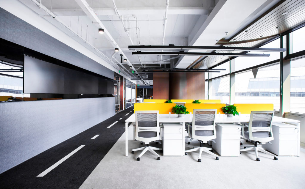 A modern office shows rows of low partition desks and chairs next to a strip of hallway made to resemble a blacktop road.