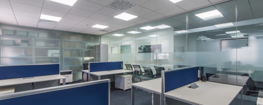 An empty modern office houses blue-paneled used office cubicles for liquidation.
