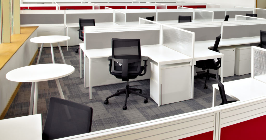 An office space houses sections of used office cubicles in white and red, acquired from used office cubicles liquidation.