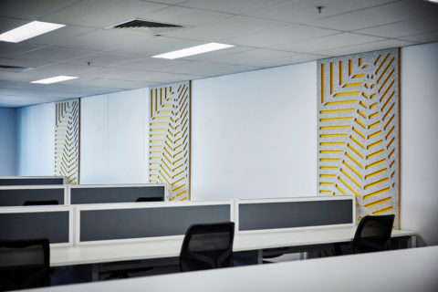 Modern office cubicle workstations with lower gray panels in a contemporary office.