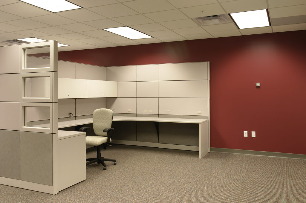 A white modern office cubicle and panel system in an office with a red wall.