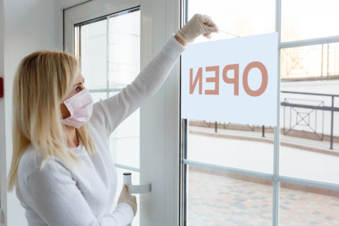 A blonde female business owner in a white shirt wearing a pink face mask posts an open sign in the window.
