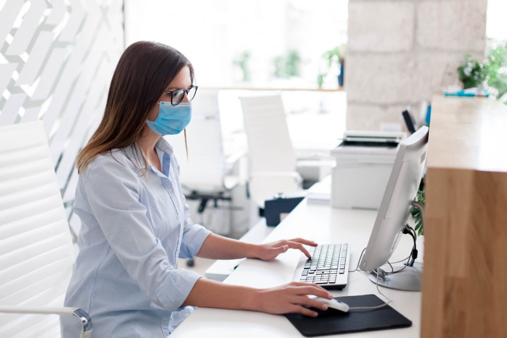 A female with brown hair and glasses wears a medical mask at her desk with a terrace panel social distancing office product.