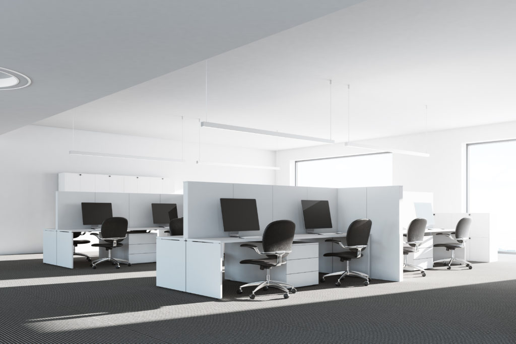 A modern office with white cubicle clusters and black office chairs.