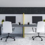 Two cubicle workstations side-by-side are separated by a yellow panel system, accompanied by white-rolling chairs.
