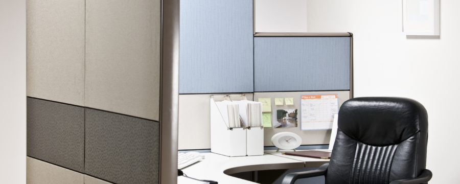 A stand-alone, modern cubicle and panel system with a comfortable, black office chair.