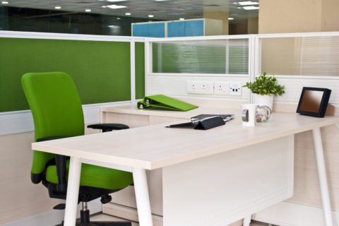 A modern cubicle shows a green acrylic workstation panel and frosted acrylic workstation screen surrounding a white desk.