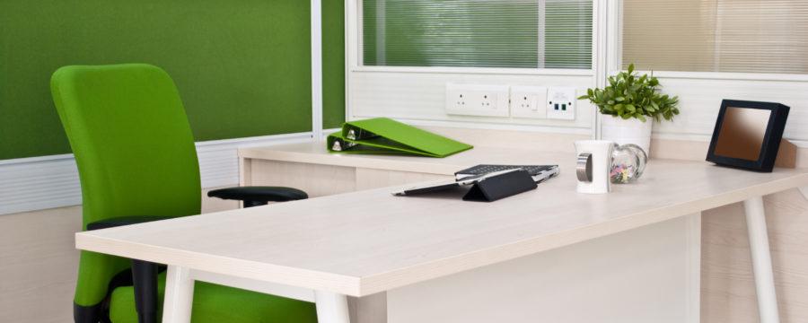 A modern cubicle shows a green acrylic workstation panel and frosted acrylic workstation screen surrounding a white desk.
