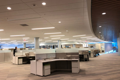 A modern office features several cubicle-cluster workstations.