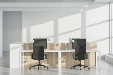 A modern office workstations cubicles grouping, back-to-back with desktop computers and black swivel chairs.
