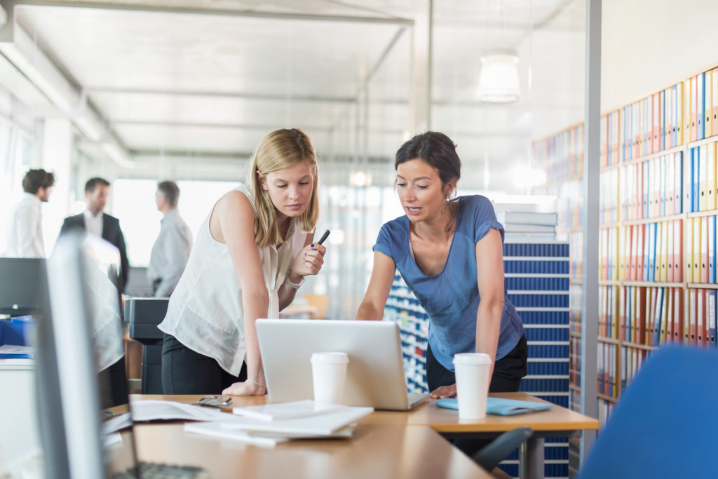 Two female small business owners look at laptop and discuss how to save money on preowned office furniture.