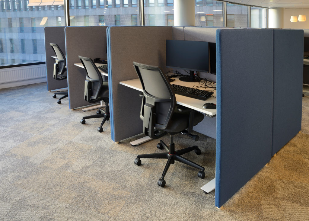 Office with blue cubicle workstations, black chairs, and large picture windows.