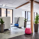 Modern office filled with natural light, contemporary furniture, and moveable gray partition walls enclosing workspace.