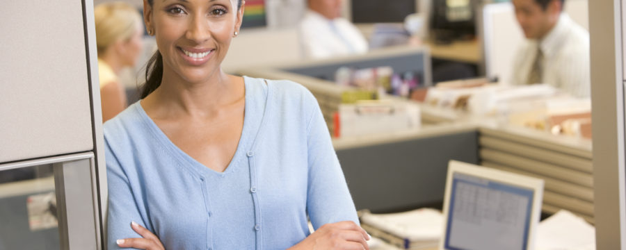 African american businesswoman standing in a cubicle door smiling in front of a busy office
